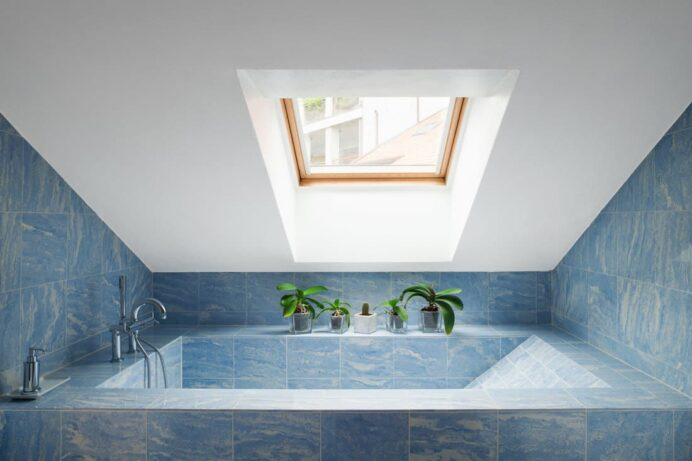 A-modern-attic-with-a-blue-tiled-bathtub-and-white-ceilings-and-a-sunroof Ceiling Inspiring Bathroom Ceiling Ideas